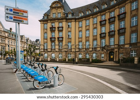 LUXEMBOURG, LUXEMBOURG - JUNE 17, 2016: Row of city bikes for rent on a background of bank building Banque et Caisse d'Epargne de l'Etat