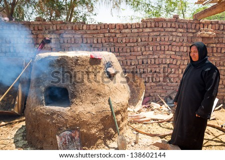 LUXOR, EGYPT - APR 10: Unidentified arabic woman baking bread in the bedouin village near Luxor, on 10 Apr 2013. This is traditional lifestyle for many people in this region of Egypt. - stock photo