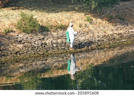 LUXOR, EGYPT-JAN. 12: An Egyptian man fishes for tilapia along Egypt's Nile River on Jan 12, 2009.   - stock photo