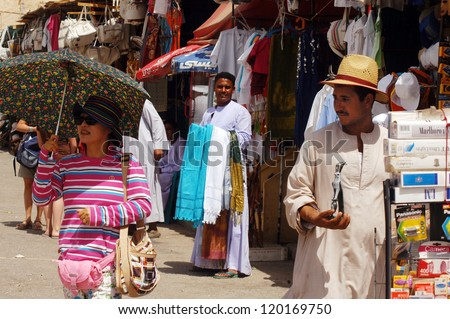 LUXOR - MAY 02:Egyptian men and tourist in the market on May 02 2007 in Luxor  Egypt.The number of tourists visiting Egypt dropped by more than a third since the Egyptian revolution on Jan 25 2011. - stock photo