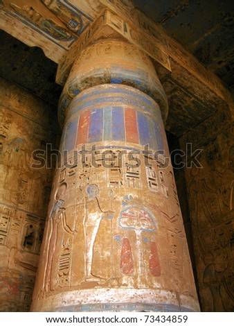 Luxor: Polychromed column with bass-reliefs at the temple of Medinet Habu, dedicated to Rameses III. West bank, Luxor, Egypt - stock photo