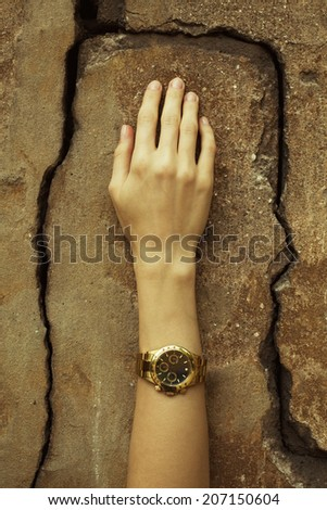 Luxurious accessory concept. Young woman's hand wearing a golden watch with golden strap over cracked stone wall. Perfect manicure. Vintage style. Close up. Outdoor shot - stock photo
