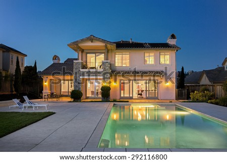 Luxurious and modern house with deckchairs, swimming pool at night. - stock photo