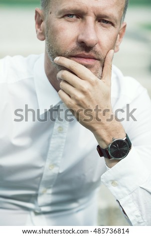 Luxurious and stylish concept. Smiling rich mature man sitting and looking at camera. Premium class clothing, expensive wrist watch, excellent manicure. Classic style. Close up. Outdoor shot