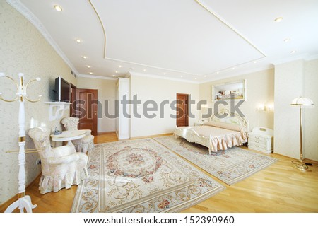 Luxurious bedroom with beautiful double bed, with armchairs and TV in classic style. - stock photo