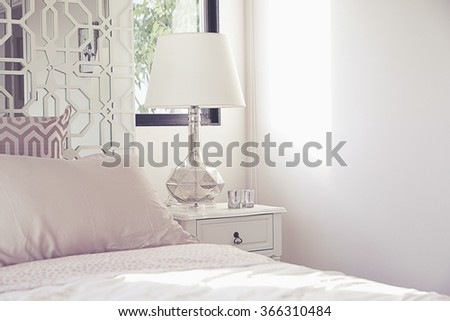 luxurious bedroom with lamp on bedside table - stock photo