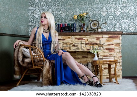 Luxurious blonde woman in a blue dress in front of classical room