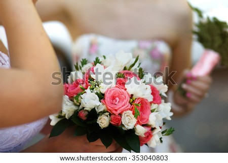 Luxurious bouquet of roses in hands of the bride in a beautiful dress on the street. Floral composition.