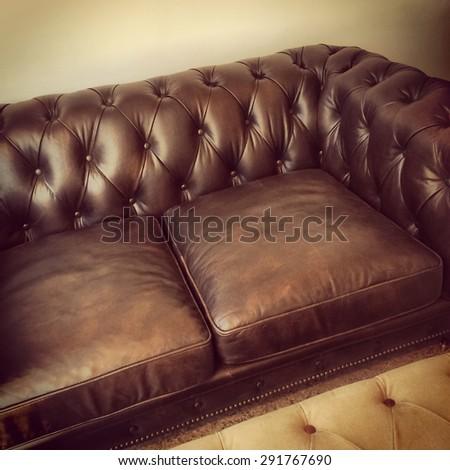 Luxurious brown leather sofa. Retro style furniture. - stock photo