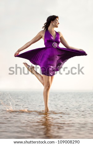 Luxurious dancing woman on the background of the sea, outdoors