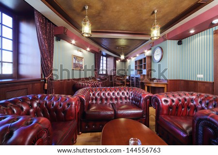 Luxurious english cigar room with leather armchairs and wooden round table.