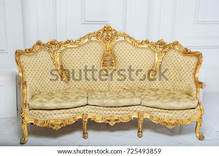 Luxurious Golden Sofa On A Background Of Old White Wall