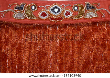 Luxurious handmade belt embroidered with red, black, silver and golden beads - stock photo