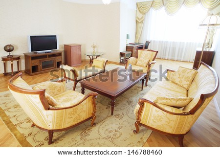 Luxurious living room with armchairs, sofa, wooden table and TV in classic style. - stock photo