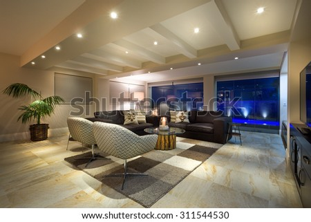 Luxurious living room  with big windows, couple of sofas and armchairs - stock photo