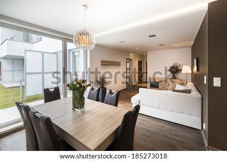 Luxurious living room with dinning table and big window - stock photo