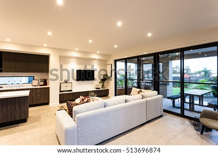 Luxurious Living Room With Sofas Televisions And Kitchen Beside Entrance To The Outside Patio Area