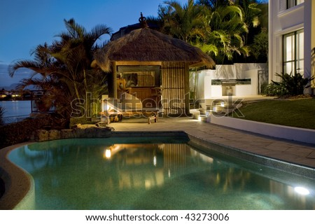 Luxurious mansion exterior at dusk overlooking pool and Bali hut