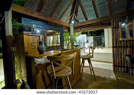 Luxurious mansion exterior at dusk with Bali hut and bar