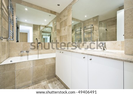 Luxurious marble bathroom with a large classy bath and double wash basin - stock photo