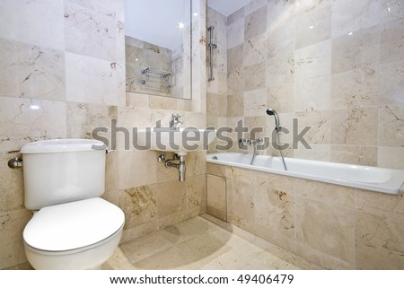 Luxurious marble bathroom with a large classy bath, wash basin and toilet - stock photo