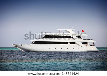 luxurious modern private yacht anchored at sea - stock photo