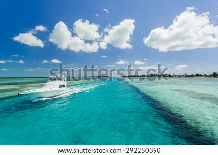 Luxurious motor boat in the Bahamas with turquoise water and blue sky  - stock photo