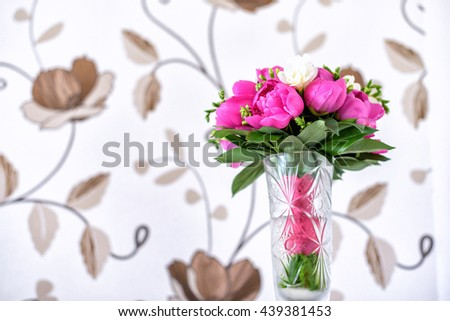 Luxurious pink, red and white peonies bouquet with leaves and buds in the crystal vase