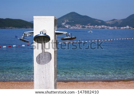 Luxurious public beach shower on a sandy sea coast as a concept for cooling down in the summer heat - stock photo