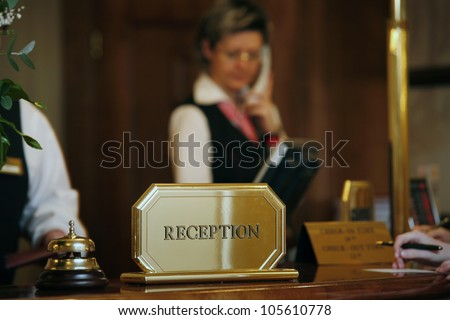 luxurious reception area with receptionist phoning - stock photo