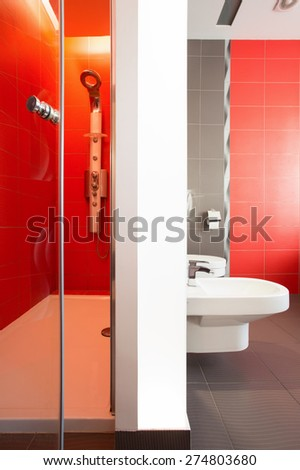 Luxurious red bathroom with spacious shower - stock photo