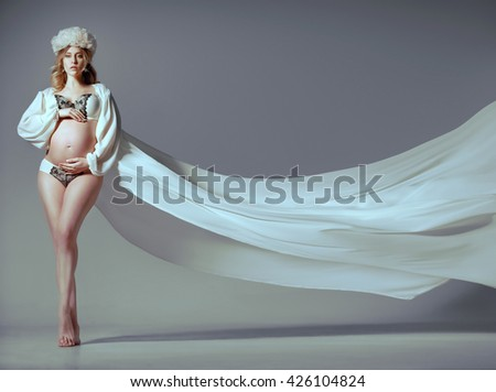 Luxurious slim high pregnant blonde dressed in fashionable underwear and a long white silk robe. Color beautiful headdress. the concept of fashion for pregnant women. make good, healthy skin. - stock photo