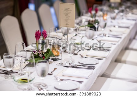 Luxurious table set up with plates and cutlery for dinner reception.