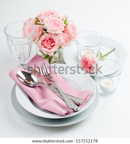 Luxurious table setting with pink roses, candles and shiny new cutlery on a white background, isolated - stock photo