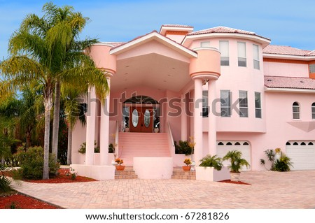 Luxurious waterfront home with double sets of columns that holds the huge arcade style roof above the stairs and up to a double door entryway. Minimal but perfect landscaping for an ultra modern home. - stock photo
