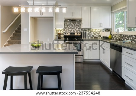 Luxurious white Kitchen in Modern Home with free space for refrigerator  grey granite counter tops wooden floor, kitchen island and all new new stainless steel appliances. - stock photo