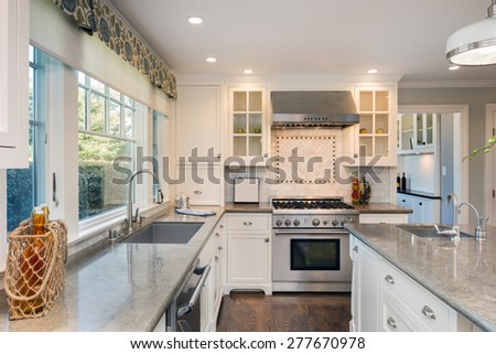 Luxurious white Kitchen in Modern Home with granite counter tops, wooden floor, kitchen island with deep sink and all new new stainless steel appliances. - stock photo