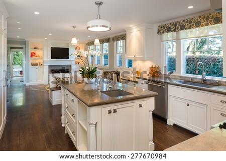 Luxurious white Kitchen in Modern Home with granite counter tops, wooden floor, kitchen island with deep sink and all new new stainless steel appliances. Open designer kitchen with fitting cabinets. - stock photo