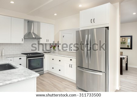 Luxurious white Kitchen in Modern Home with pearl white marble counter tops wooden floor, bar and double door stainless steel refrigerator. - stock photo