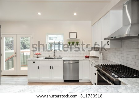 Luxurious white Kitchen in Modern Home with pearl white marble counter tops wooden floor, double french doors and all new new stainless steel appliances. - stock photo