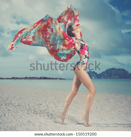 Luxurious woman in color dress on the beach - stock photo