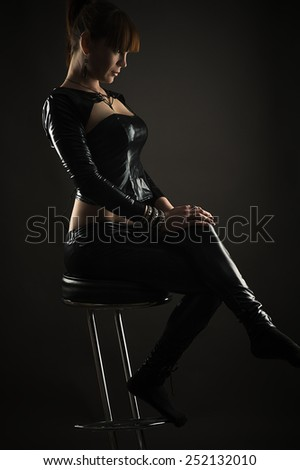 luxurious woman sitting on a bar stool in profile face - stock photo