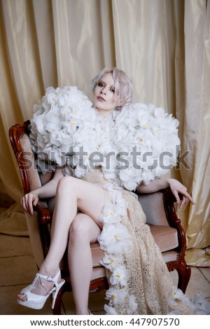 luxurious woman sitting on chair, girl in white long dress. Lifting leg, alluring look into camera, darkness to the left behind curtain, place for your text - stock photo