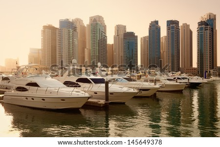 Luxurious Yachts and Boats in Front of Dubai Marina Skyscrapers, at sunset. All the logos and trade names are removed from the picture. - stock photo