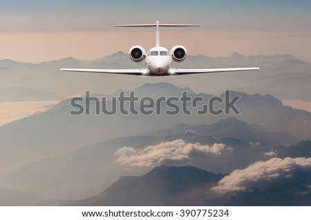 Luxury Airplane fly over clouds and Alps mountain on sunset. Front view of a big passenger or cargo aircraft, business jet, airline. Travel concept. Empty space for text - stock photo