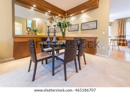 Luxury and nicely decorated dining, lunch room set, with the table and the vase with some flowers . Interior design. Vertical.