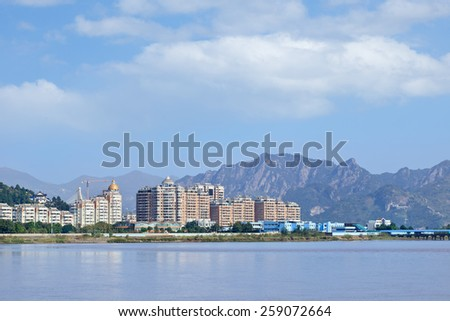 Luxury apartment buildings with river view near a mountain ridge, Wenzhou, Zhejiang Province, China - stock photo