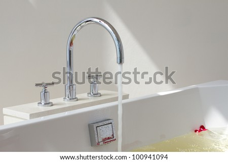 Luxury bath tub and faucet with water and flowers - stock photo