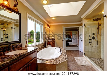 Luxury bathroom interior with skylight. Bath tub with mosaic trim and two wooden vanity cabinets - stock photo