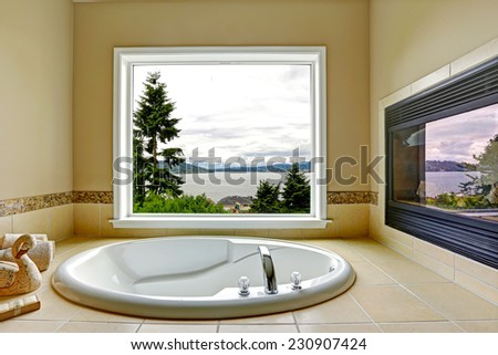 Luxury bathroom with fireplace and bay view. White bath tub with beige tile trim - stock photo